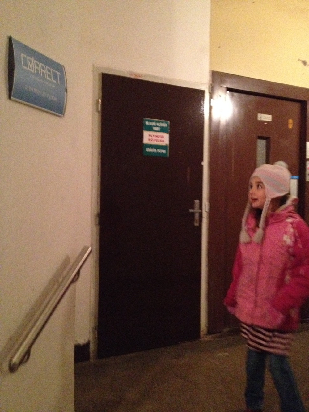 "Our school is called ""Correct"" and is located in a typical, old and, well, fairly dingy building in the square.  Here Hannah is glancing at the sign."