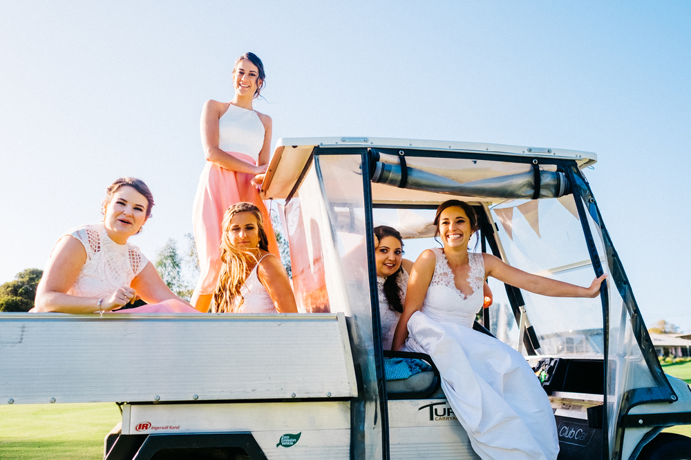bride-and-bridesmaids-on-a-golf-buggy-laughing-on-at-the-boys-on-the-golf-course-Emily.jpeg