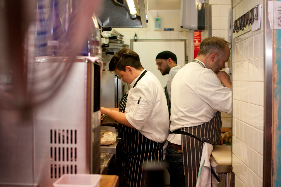 Emma, Kacper and Craig Sandle close at work in the tiny kitchen of Juveniles