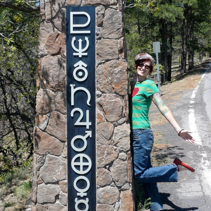 """Me at the gates to the observatory in Flagstaff, AZ where Pluto was discovered. The """"P"""" at the top is Pluto's glyph!"""