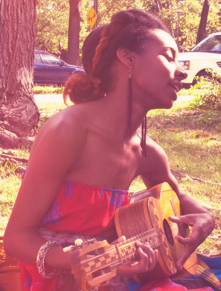 Singing a song, strumming her Venezuelan cuatro