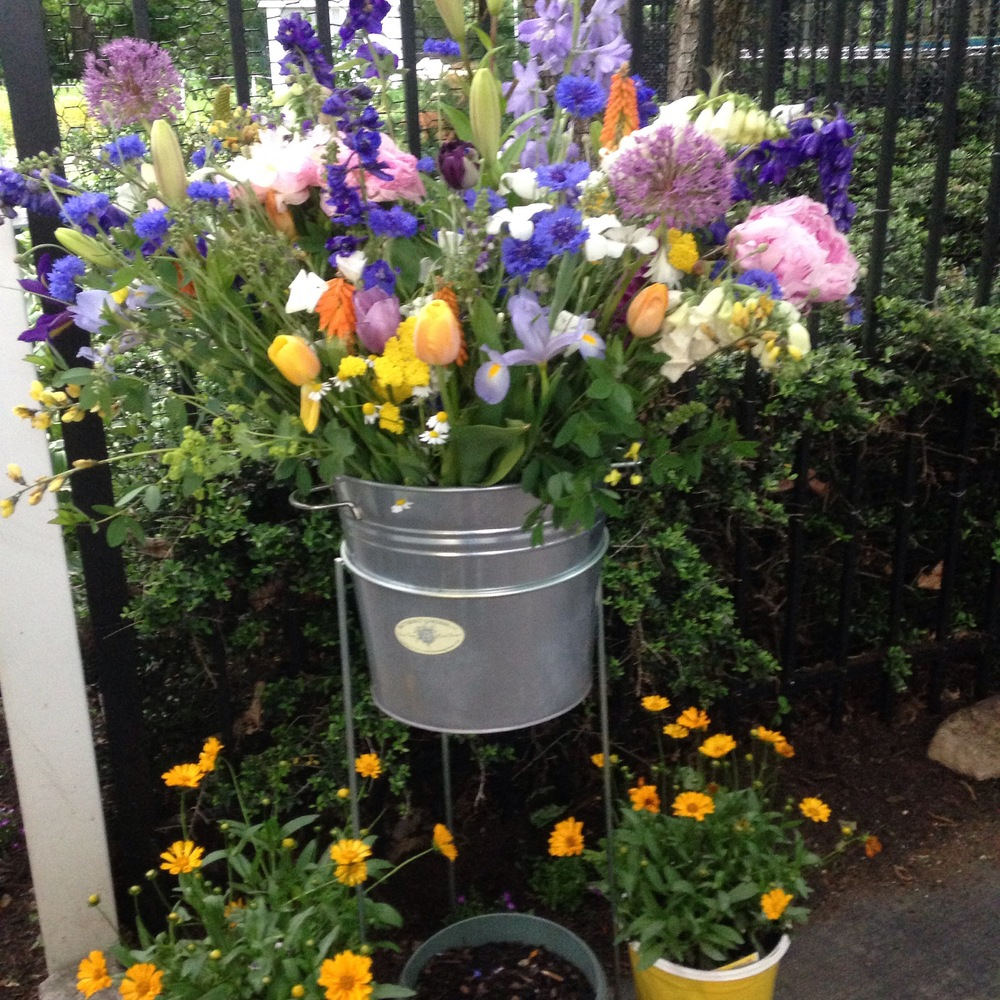 One of the buckets of flowers placed near the entrance to the back gardens to welcome visitors yesterday during the Westport Historical Society's Hidden Gardens Tour.