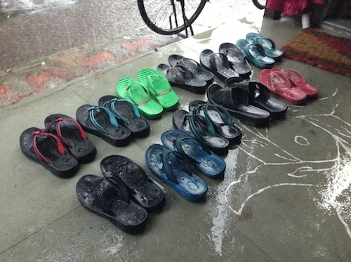 Sandals lined up neatly on a rainy day class.