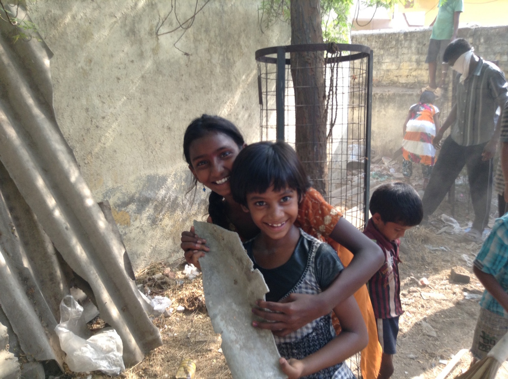 Laxmi and Anjali smiling while they work.