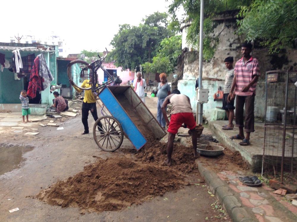 Community members manually transport soil to the garden.