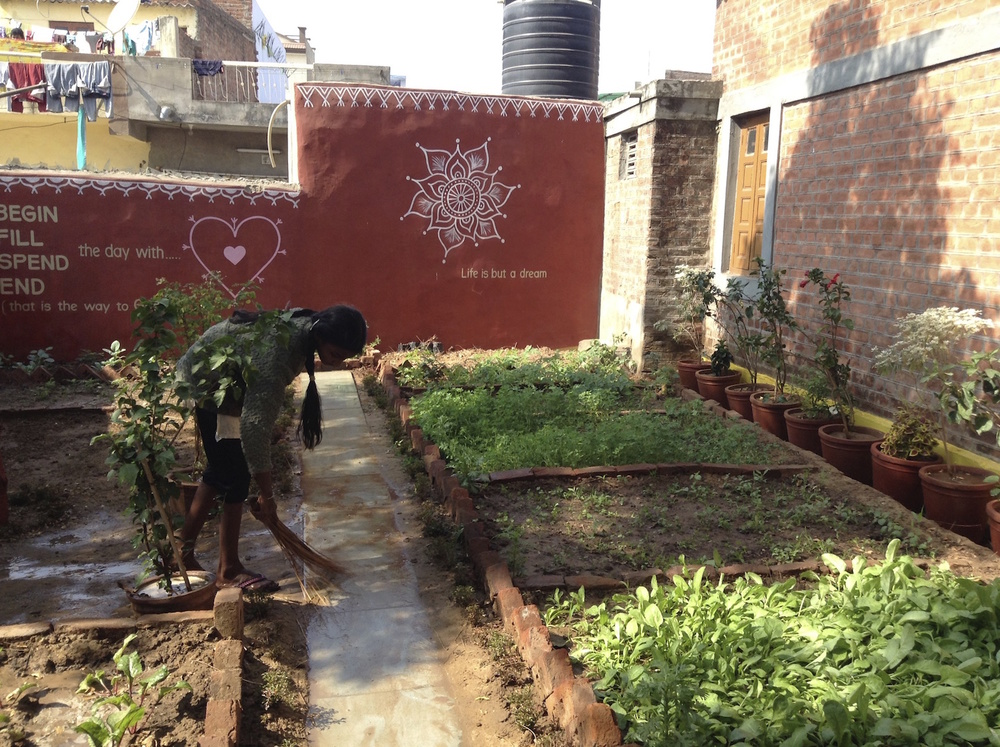 Laxmi voluntarily cleans and waters the garden each day.