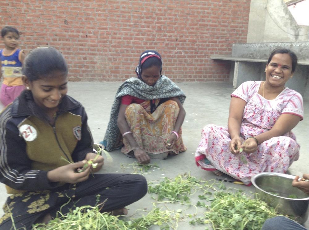 Anu, Pulabhen, and Jyotibhen prepare vegetables for the dinner program.