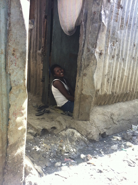 A Kitui resident with sewage outside of her home.