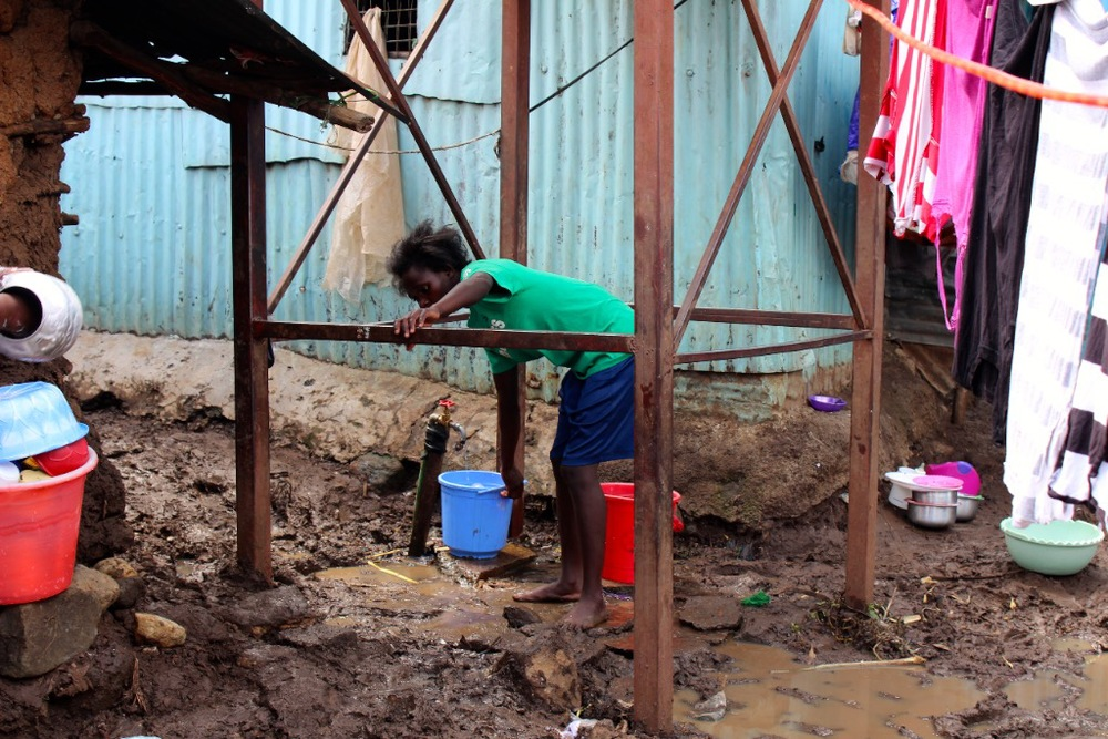 A resident filling up at Malezi's water tank.