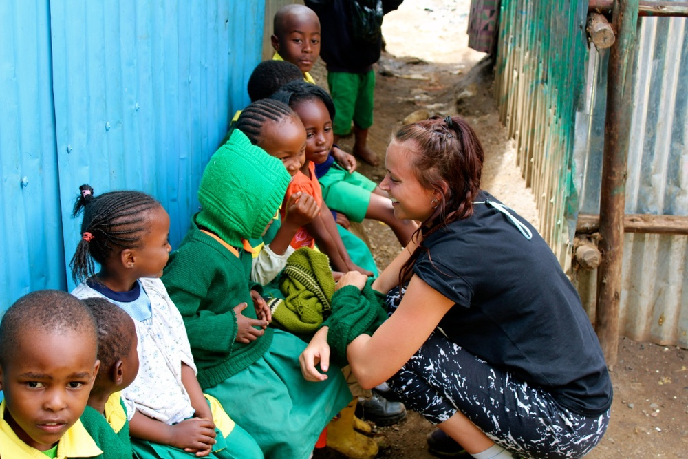 A volunteer from Denmark visits with the kids.