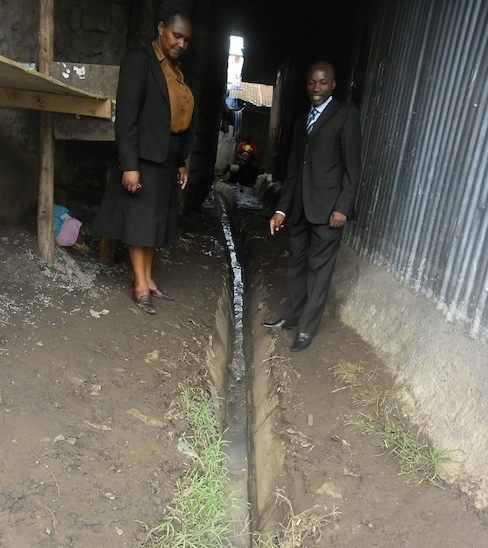 Teacher Grace Kavoi and Jared Akama inspecting one of the trenches.