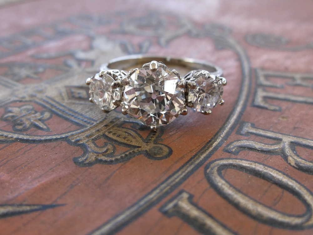 SOLD - Mesmerizing early 1900's three stone Old European cut diamond ring! The center diamond is 2.30 carats with a 0.58 carat diamond on either side