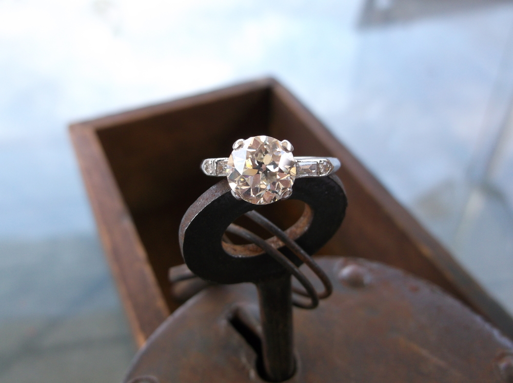 SOLD - A gorgeous older take on the classic engagement ring style! Beautiful 1930's Old European cut 2.00 carat diamond set in a platinum mounting with a small baguette and round diamond on each side