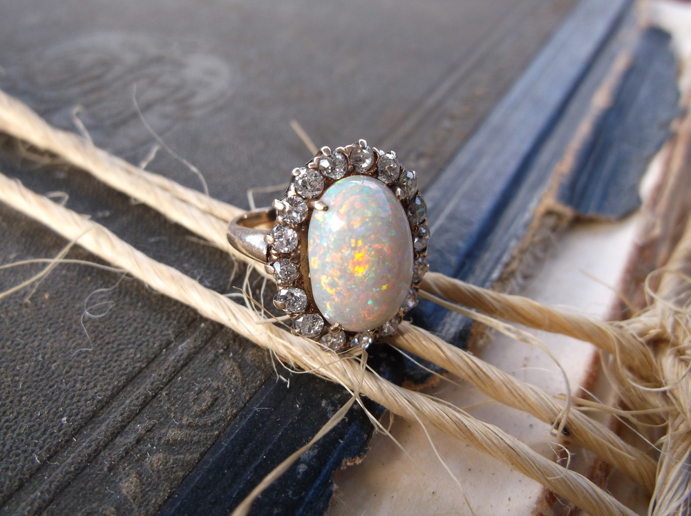 Scintillating turn of the century opal ring set in yellow gold, surrounded by 0.85 carats total weight in old mine cut diamonds!