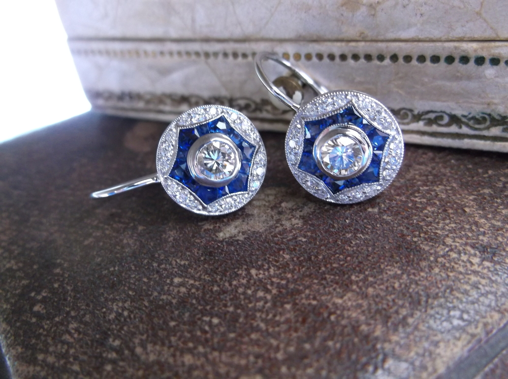 SOLD - Stunning slight drop, circular diamond and sapphire earrings. The total carat weight for the two center diamonds is 0.46 carats. The total carat weight for the sapphires is 0.90 carats.