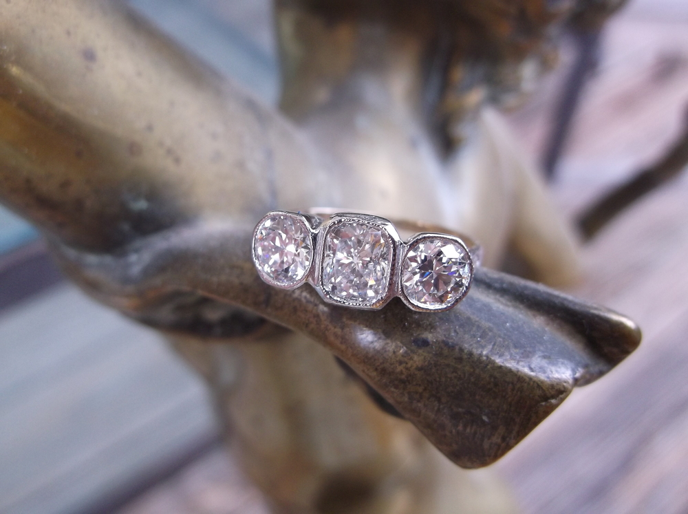 SOLD - Exquisite Art Deco style platinum and 18K gold ring with three gorgeous diamonds, the center having 0.71 carats with a 0.50 carat on each side!