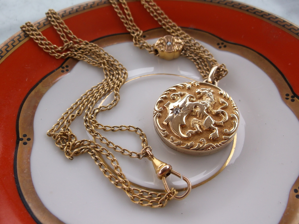 SOLD - Stunning gold Victorian lion locket with an inset old mine cut diamond on a beautiful gold Victorian watch chain with a gold and pearl hand engraved slide!