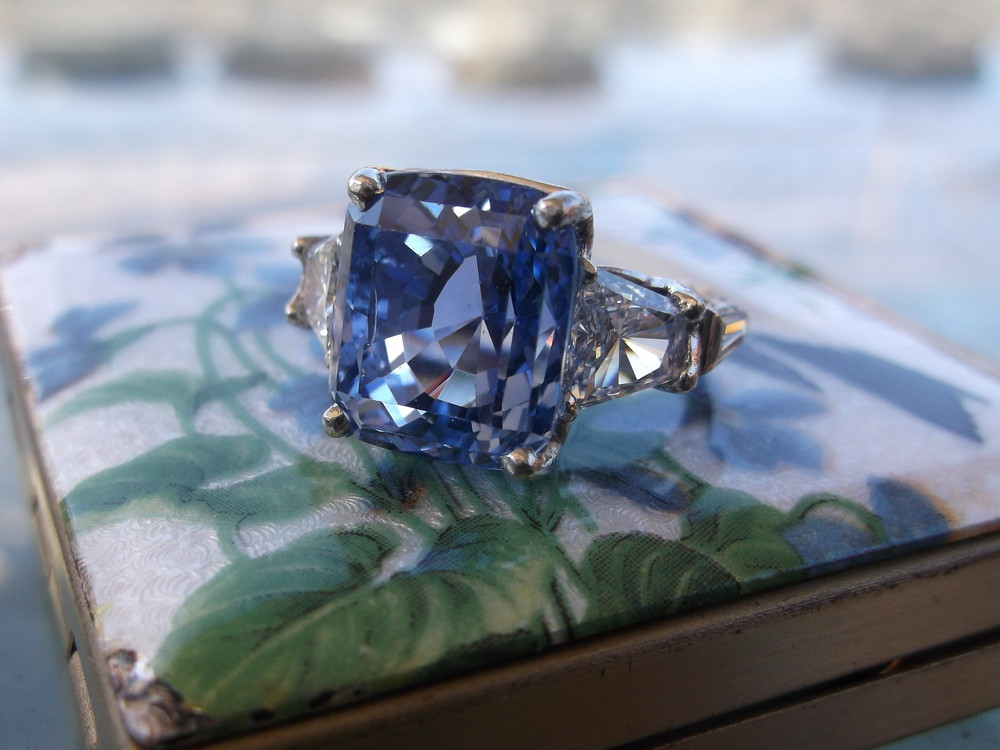 SOLD - Vibrant 9.50 carat Ceylon Sapphire set in a beautiful platinum mounting with 1.25 carats total weight in diamond baguettes and diamond trapezoids on each side.