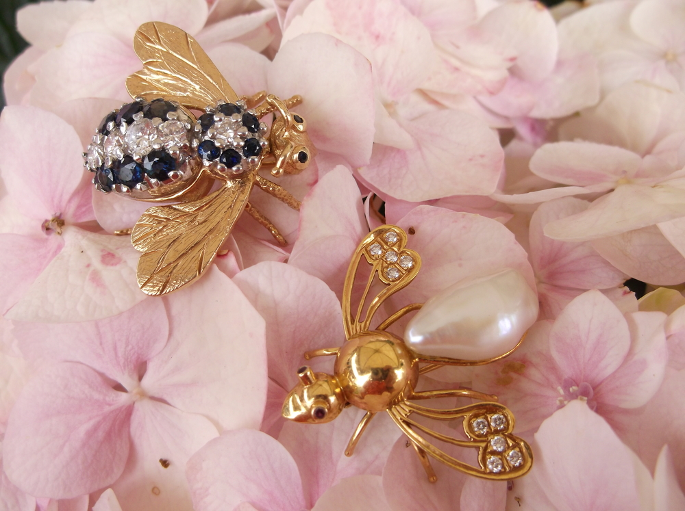 Beautifully unique insect pins! A diamond and sapphire bumble bee with 1.00 carats total weight in diamonds set in yellow gold and a diamond, ruby and Baroque pearl wasp set in yellow gold.    Diamond and sapphire bumble bee