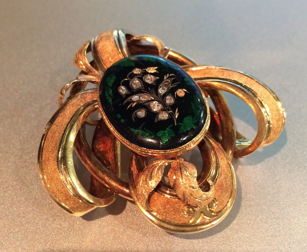 Victorian Era gold broach featuring rose cut diamonds set in black onyx with enameling details.