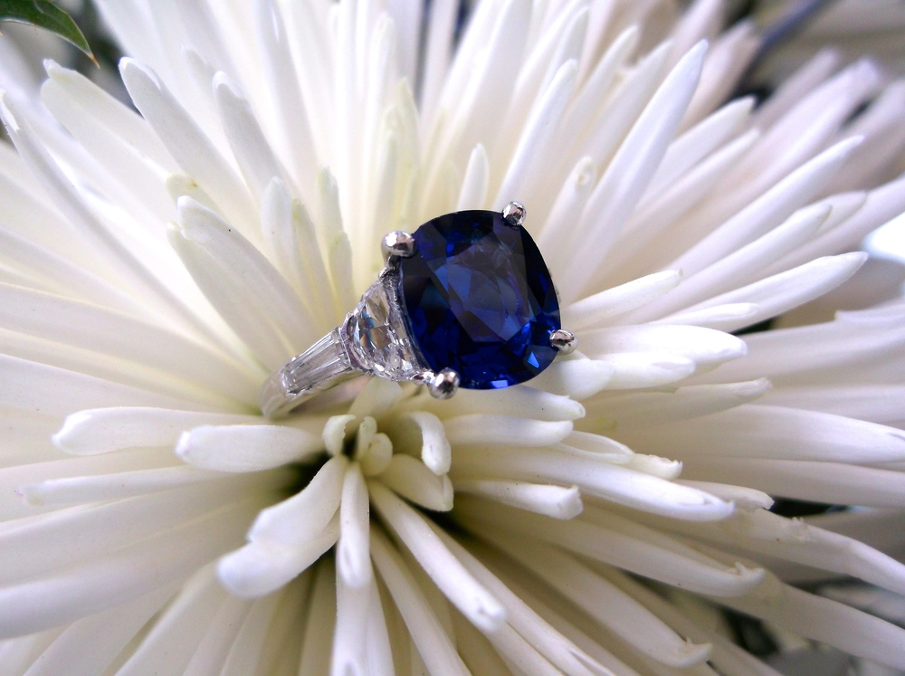 SOLD - Gorgeous 4.18 carat vibrant blue sapphire set in platinum with a baguette and half moon shaped diamond on either side.