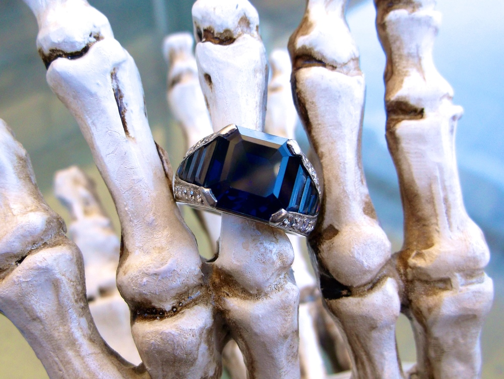 SOLD - Bewitching 8.50 carat step cut sapphire in a platinum, sapphire and diamond detail setting.