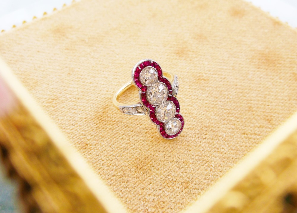Awe-inspiring Edwardian Era Old European cut diamond and ruby ring set in platinum topped gold with lovely rose cut diamond detail on either side. (1.50 carats total weight in Old European cut diamonds down the center.)