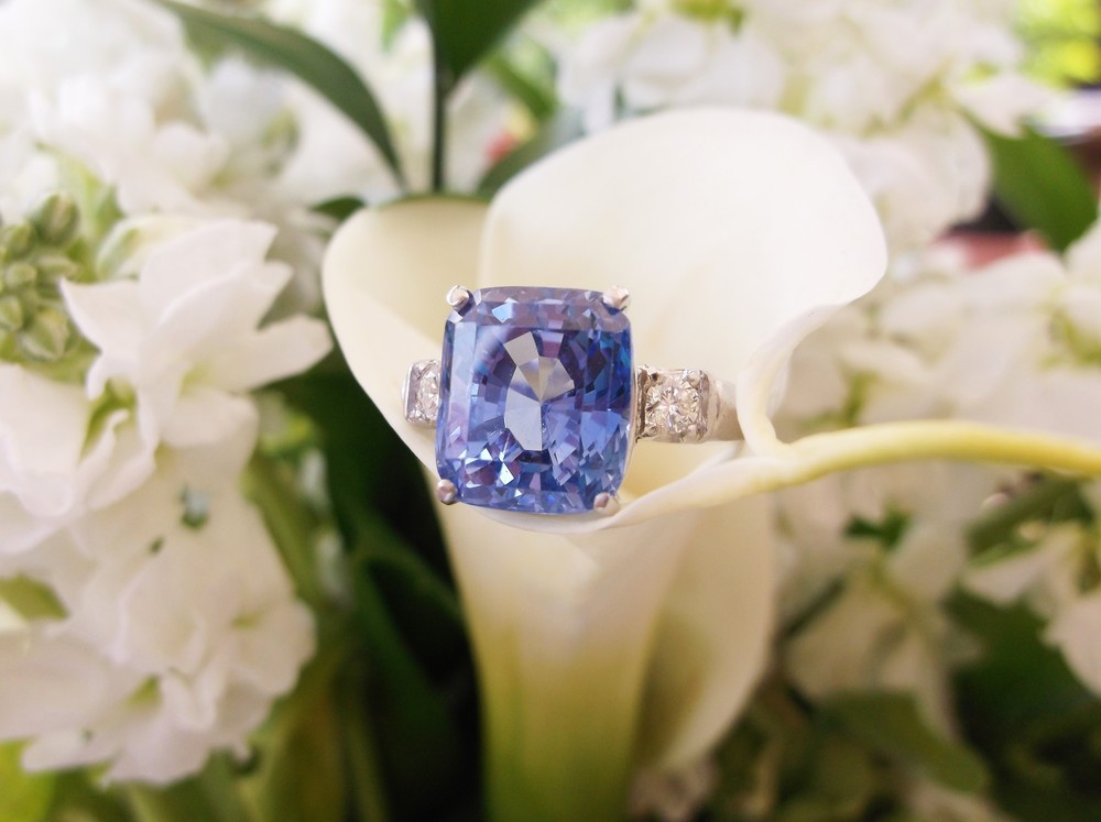 SOLD - Gorgeous 10.92 carat sapphire set in platinum with a diamond on each side.