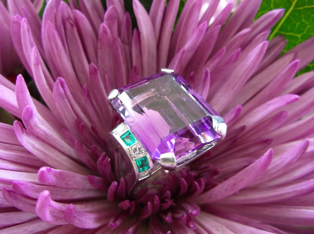 Beautiful 16.10 carat amethyst set in platinum with diamond and emerald details on each side.