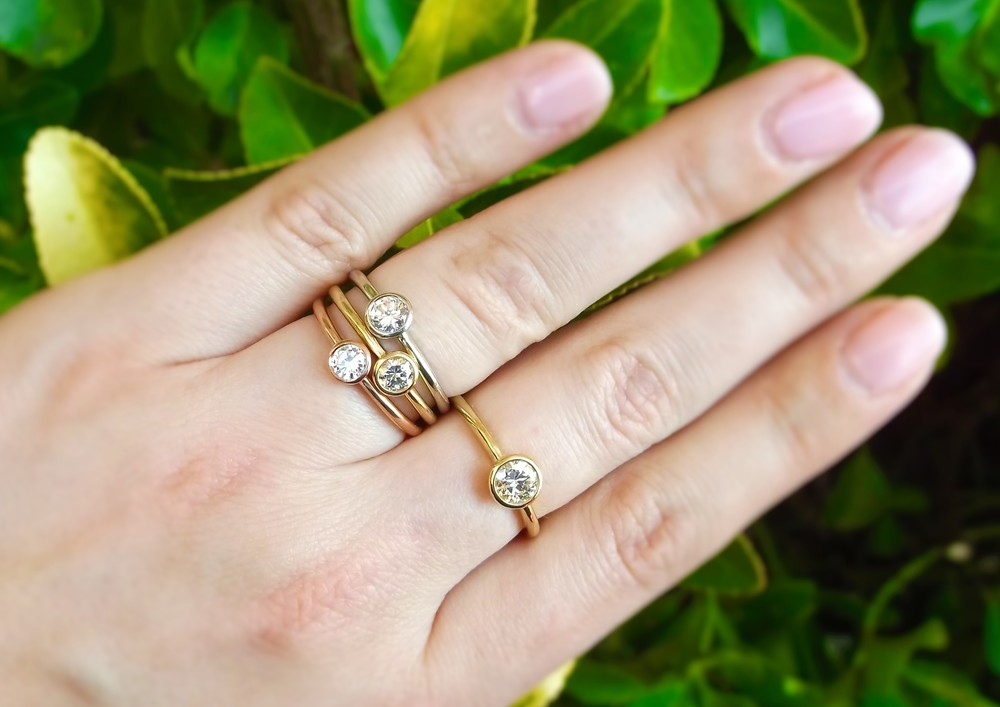 Lovely bezel set diamond rings in white gold, rose gold and yellow gold.  The diamonds set in the three stacked rings range from 0.24 carats to 0.33 carats. The individual yellow gold diamond ring is 0.54 carats.