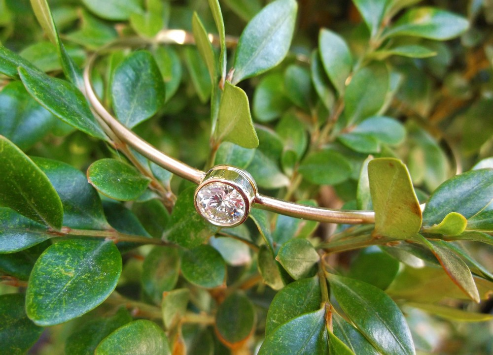 Pair this bracelet with others in your collection for effortless style or wear it on its own for a simply chic look! 0.90 carat round brilliant cut diamond, bezel set on a classic matte finished gold bangle bracelet.