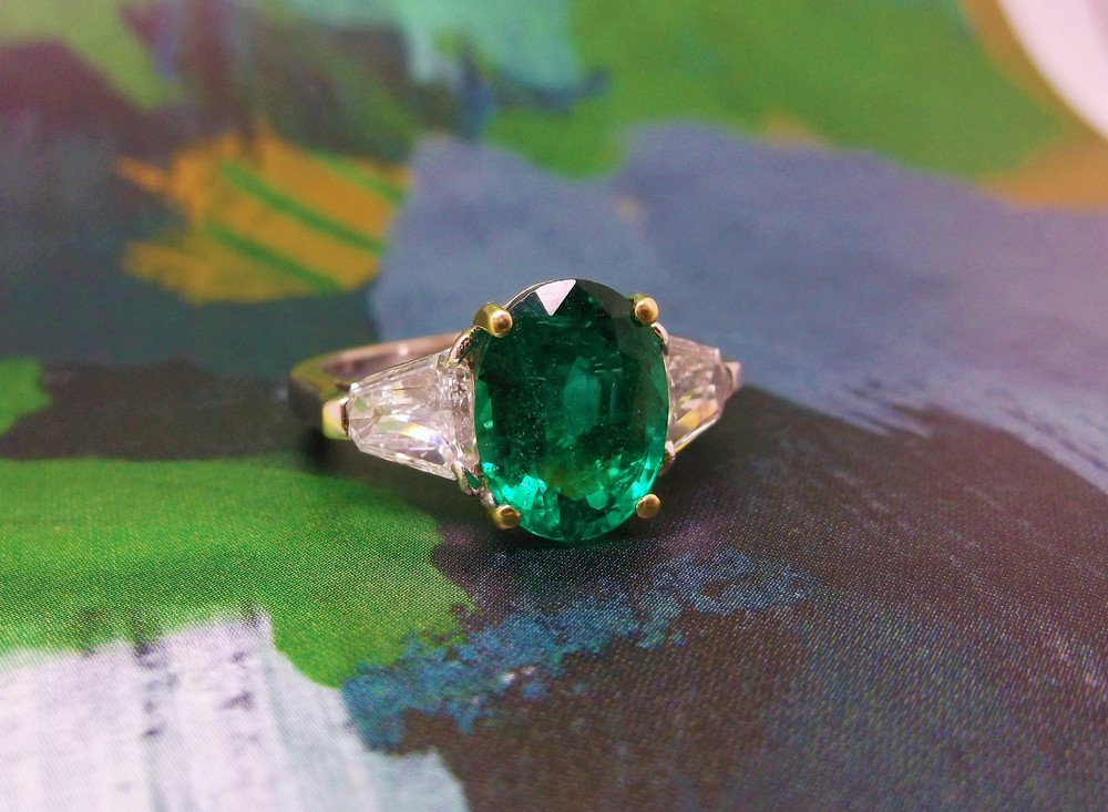 Vivacious 2.93 carat emerald with a unique 0.60 carat shield cut diamond on each side.