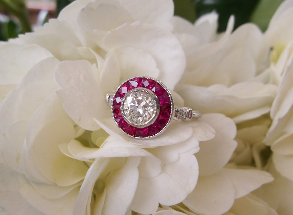 Dynamic 0.64 carat Old European cut diamond, encircled by decadent rubies.