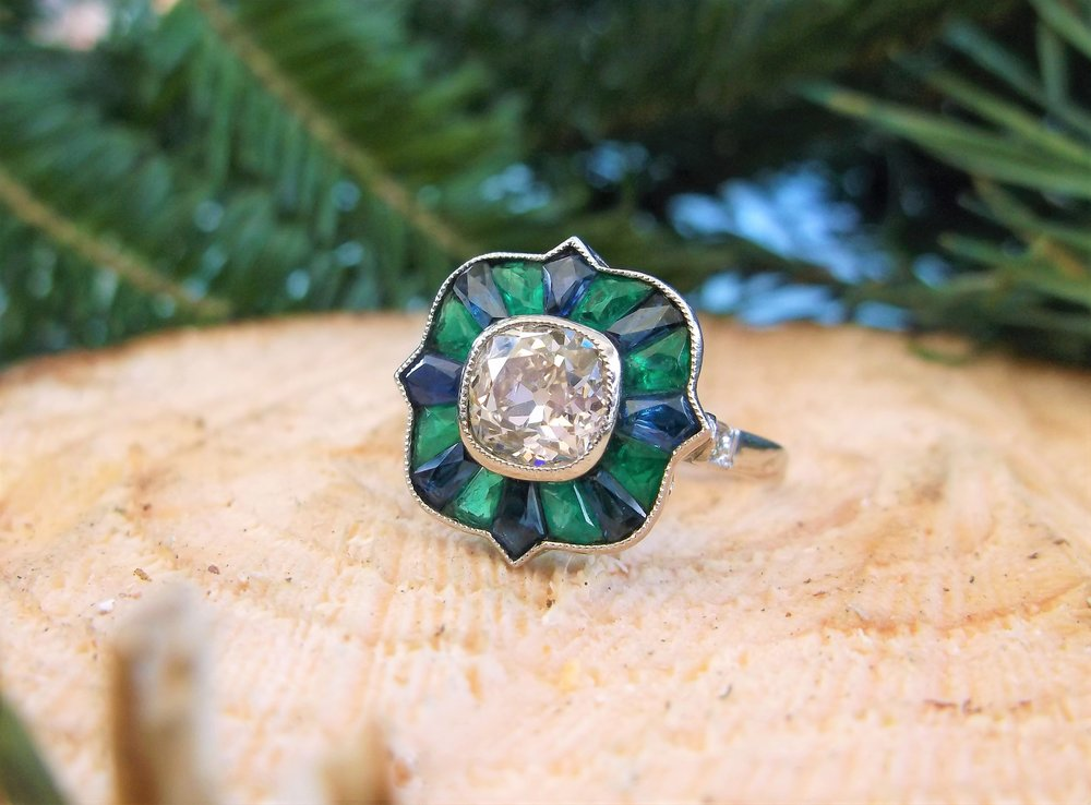 SOLD - An absolute show stopper! One of a kind 1920's ring set with a center 1.14 carat Old Mine cut diamond, surrounded by fancy cut emeralds and sapphires all set in platinum.