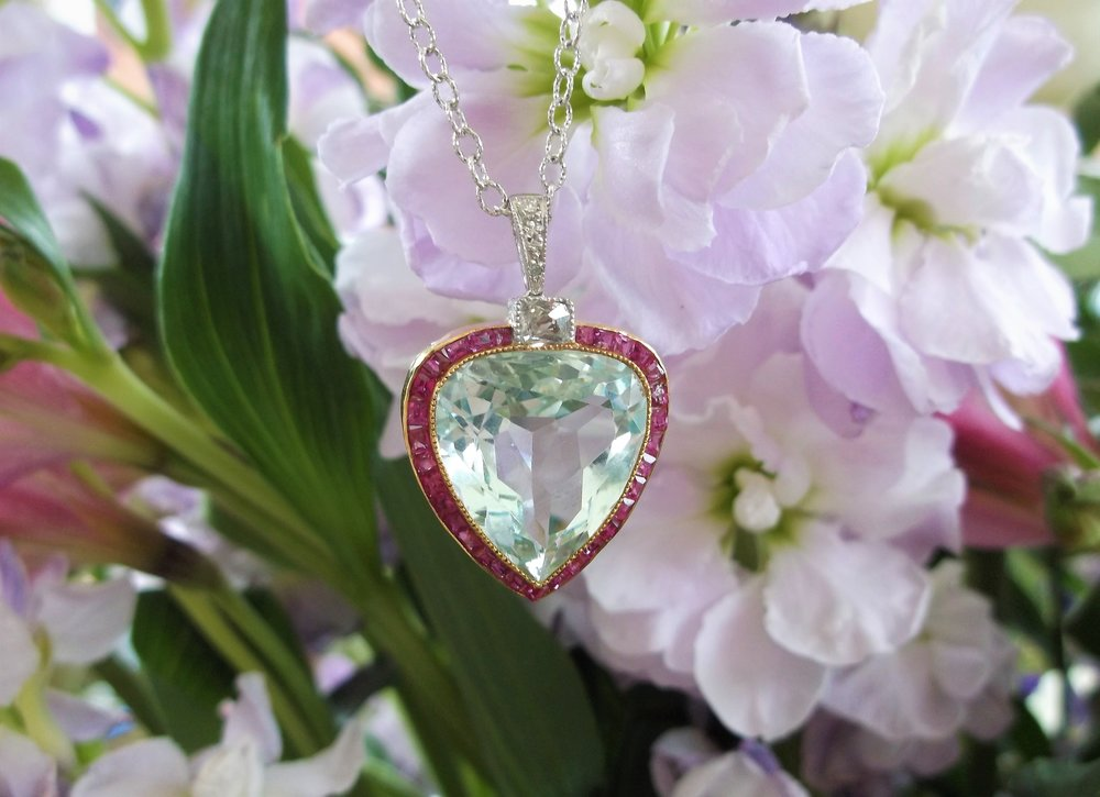 SOLD - Take her breath away with this heartfelt Edwardian era, platinum topped gold pendant, set with a gorgeous center 8.00 carat aquamarine surrounded by 1.00 carat total weight in french cut rubies and Old Mine cut diamond details.