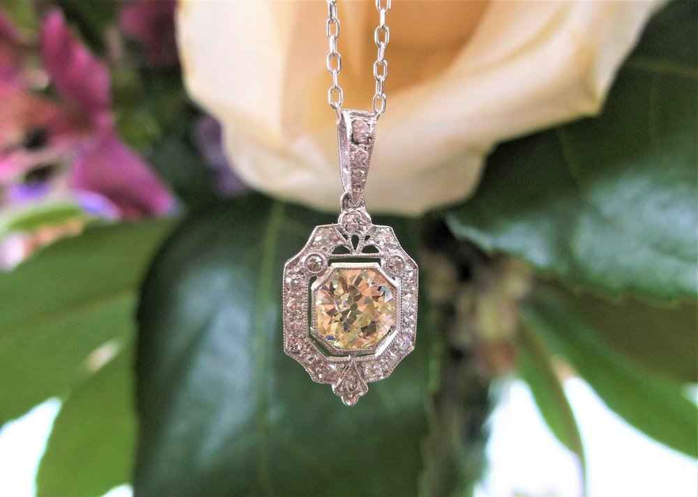 SOLD - Exquisite 1920's diamond and platinum pendant, set with a 1.00 carat Old European cut diamond in the center, surrounded by 0.45 carats total weight in Old Mine cut and single cut diamonds.