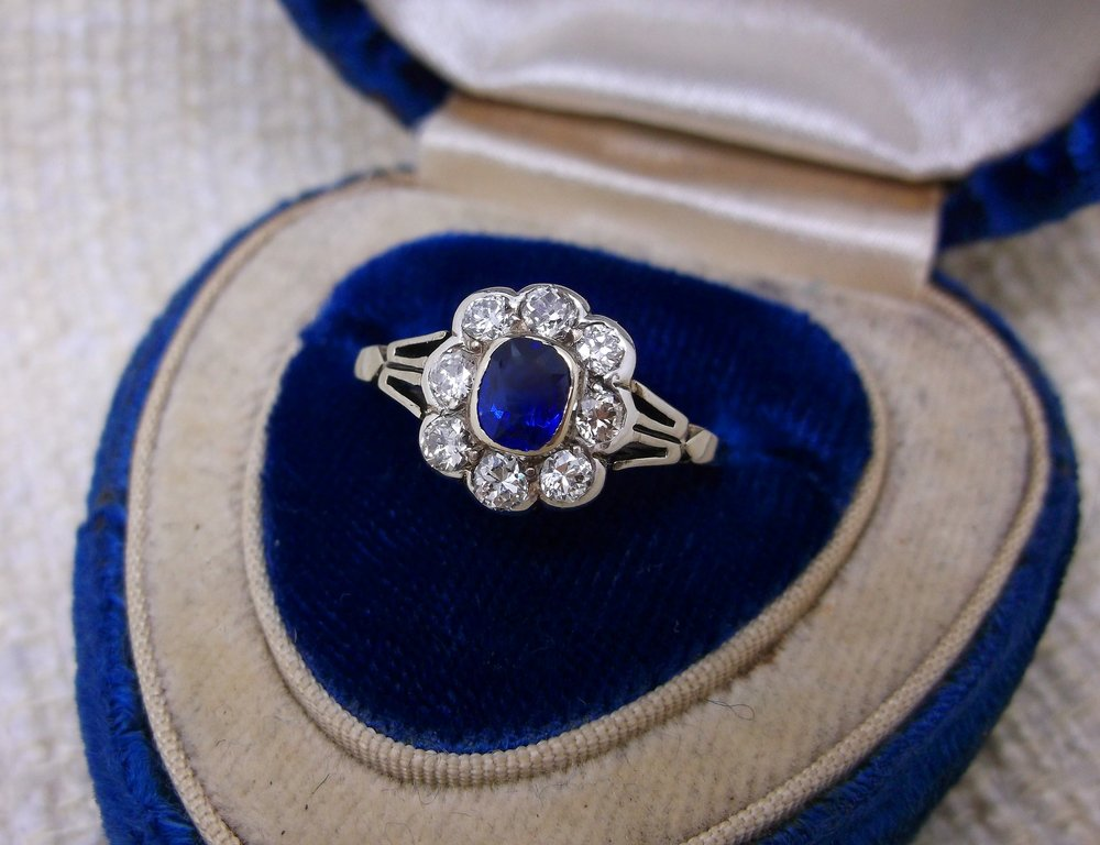 SOLD - Lovely Edwardian era diamond and sapphire ring. The ring is set with one center 0.36 carat blue sapphire, surrounded by a scalloped halo of 0.50 carats total weigh in Old European cut diamonds, all in platinum topped yellow gold.