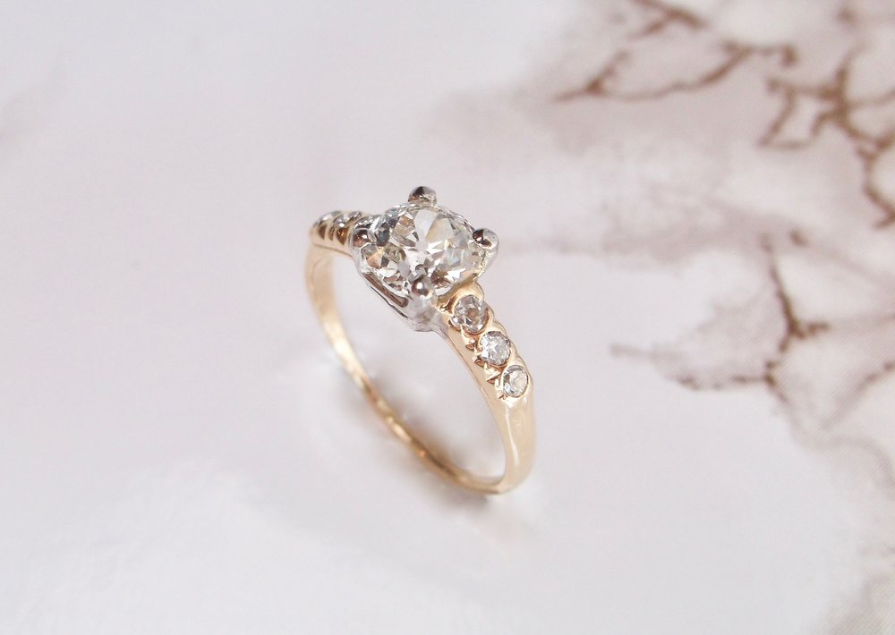 Timeless, two tone yellow gold and white gold Old Mine cut diamond ring. The ring is set with a gorgeous 0.81 carat Old Mine cut diamond, flanked on each side by three full cut round diamonds. Shop this classic look  HERE
