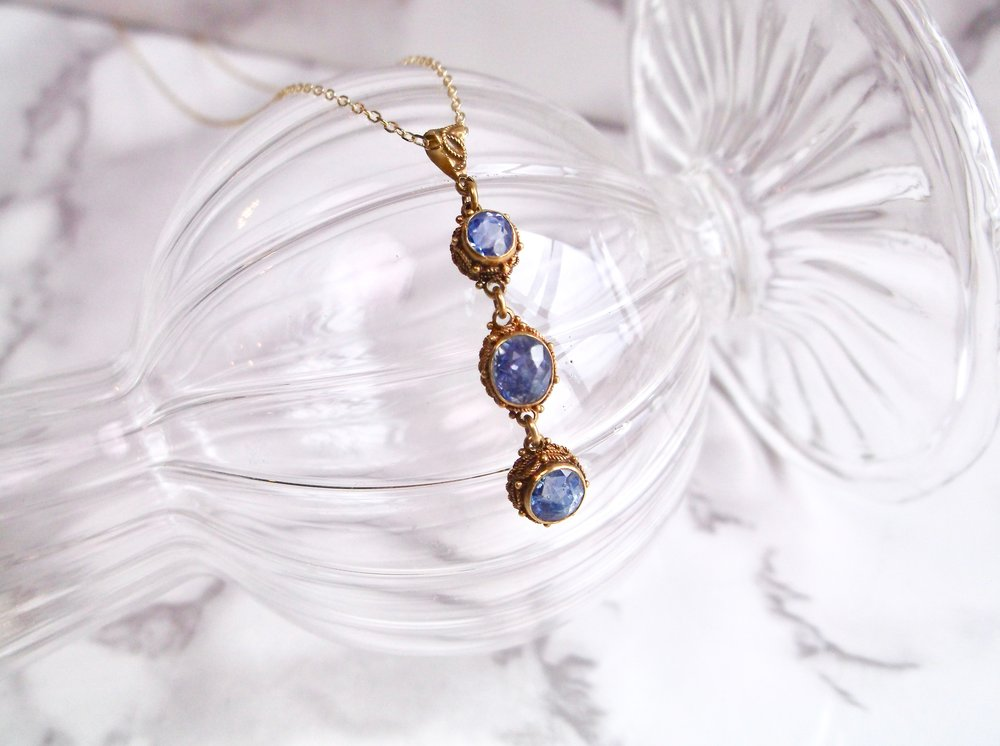 The prettiest pendant we ever did see! This lovely Victorian era drop pendant is set with three violet colored sapphires (1.00 carats total weight), each set in a detailed yellow gold bezel. Shop this pretty pendant  HERE .