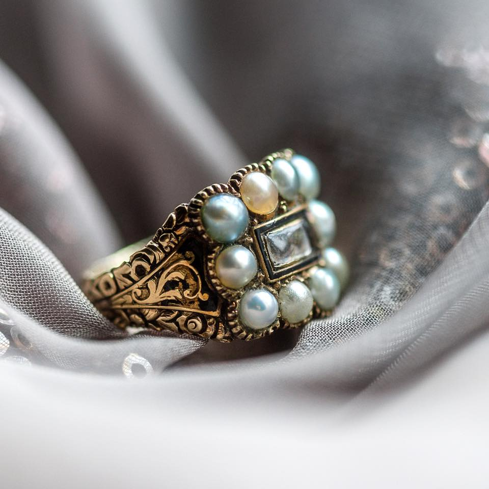 "Some may find it a tad morbid, but we find this memori mento ring utterly enchanting and a beautiful way to remember a loved one ❤️ The ring is inscribed ""Robert Richardson"" on the inside, along with gorgeous engraving, black enameling details, and a lock of braided hair surrounded by pearls. Shop this lovely piece of history  HERE ."