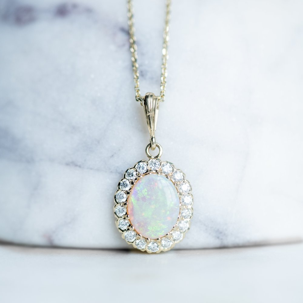 The fire in opals gets us every time! Shop this beautiful opal and diamond pendant  HERE .