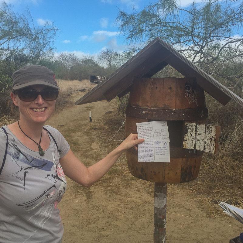 julie_posts_postcards_at_floreana_post_box_galapagos.jpg