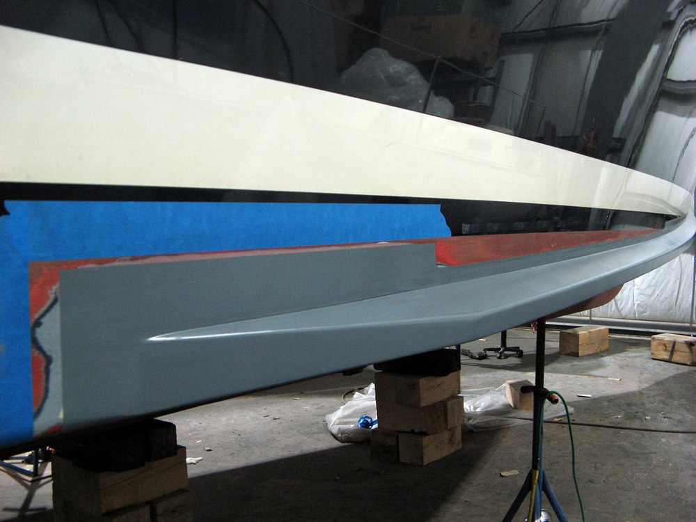Rails were then faired to the hull, epoxy sealed, and primed (shown.)