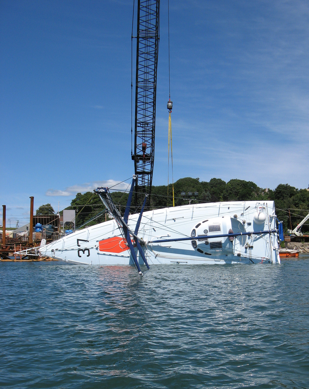 This test is done by first lifting            the boat out of the water and taking an accurate weight with a certified            load cell. When the boat is out of the water, a strop is passed around            the bulb. The boat is lowered back in the water and the crane cable            is attached to the strop. The boat is heeled over 90 degrees. With the            boat at 90 degrees, a strop is passed around the masthead. A load cell            is attached to the strop and to a fixed point, like a skiff.