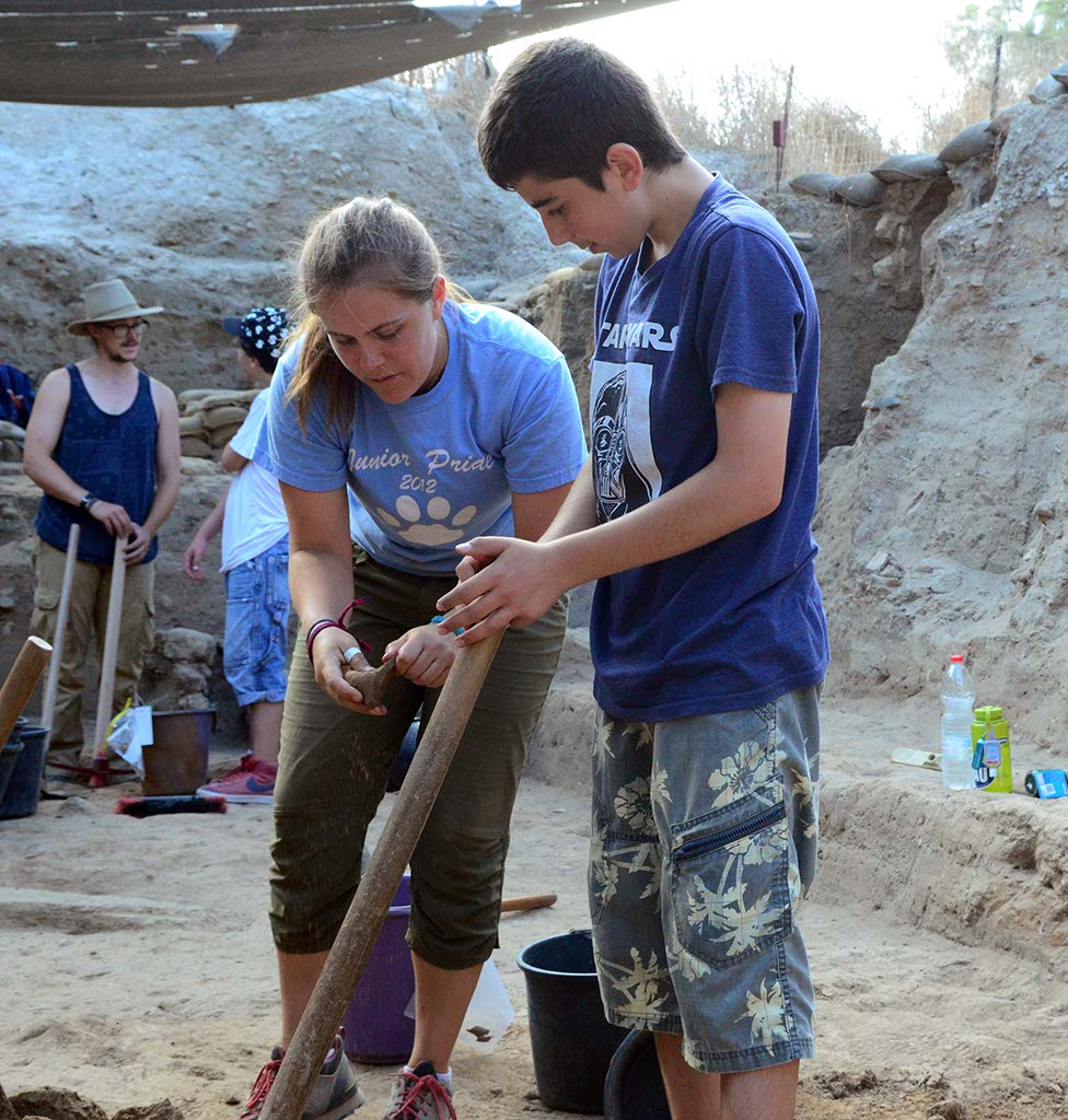 A volunteer discusses some pottery with an Israeli student