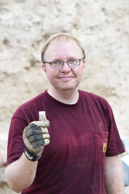 Kevin holds a piece of folded lead found in Grid 51