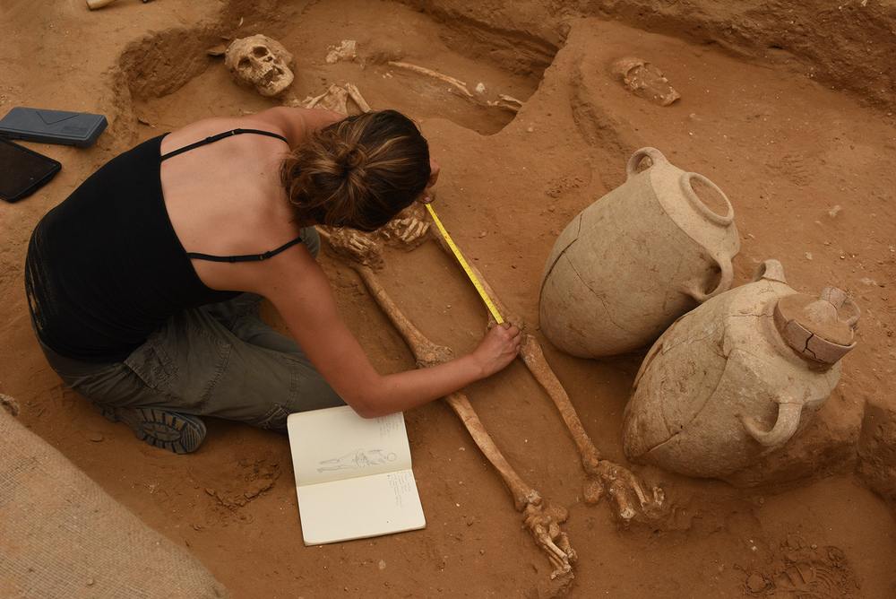 A member of the physical anthropology team, Rachel Kalisher, measures a 10th-9th century BC skeleton