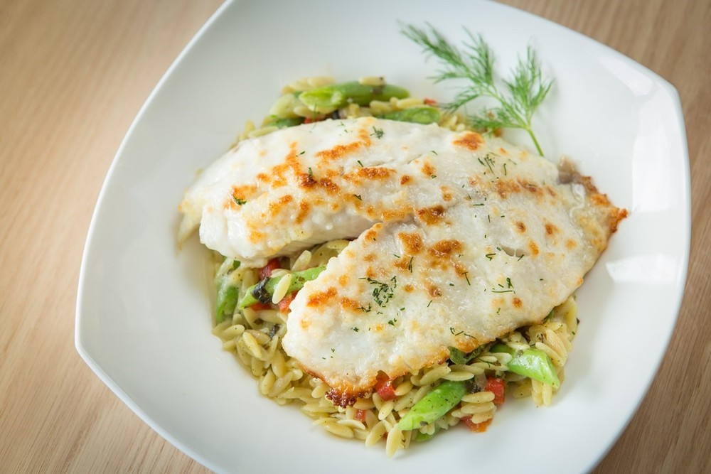 Parmesan Tilapia with Creamy Pesto Orzo and Red Peppers | Seasoned Tilapia Fillets Sprinkled with Parmesan and Served Over Orzo Pasta With BasilPesto and Roasted Red Peppers.