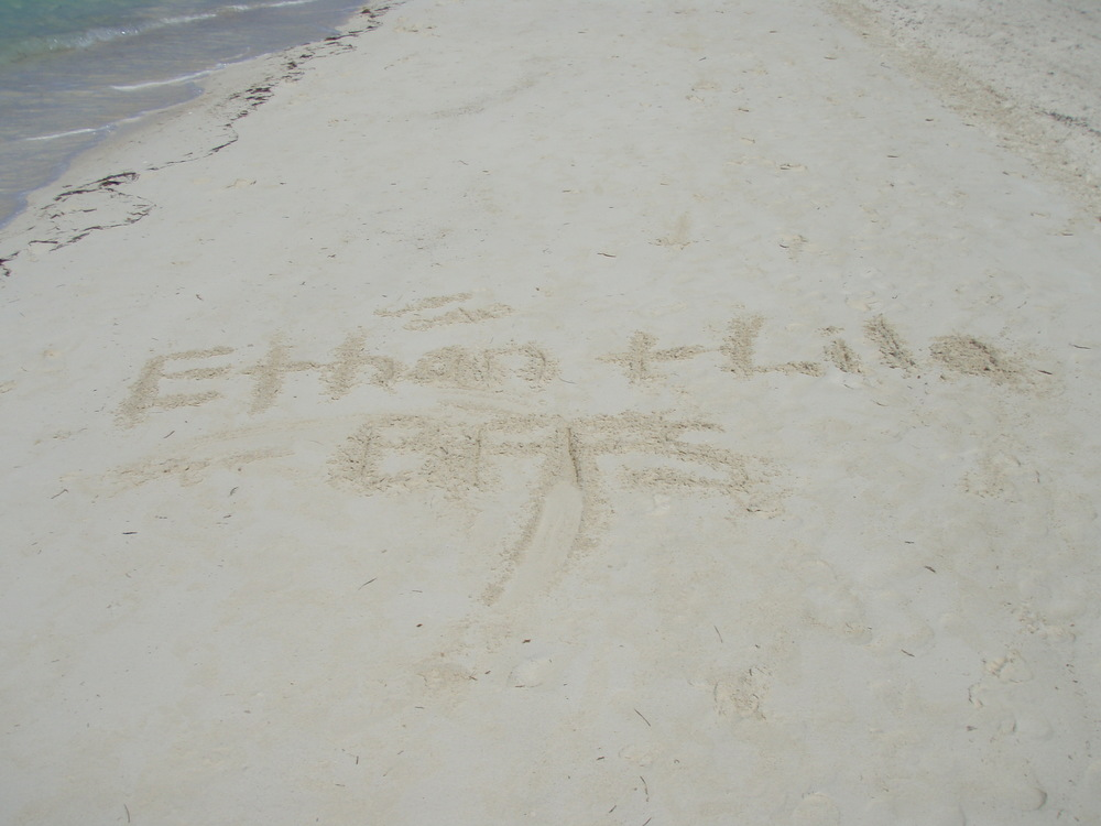 Lila and her friend Ethan's name in the sand