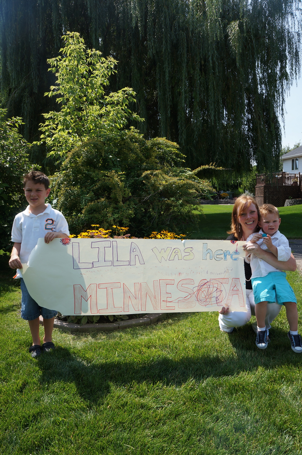 Lila stone with new friends in Minnesota and her own sign